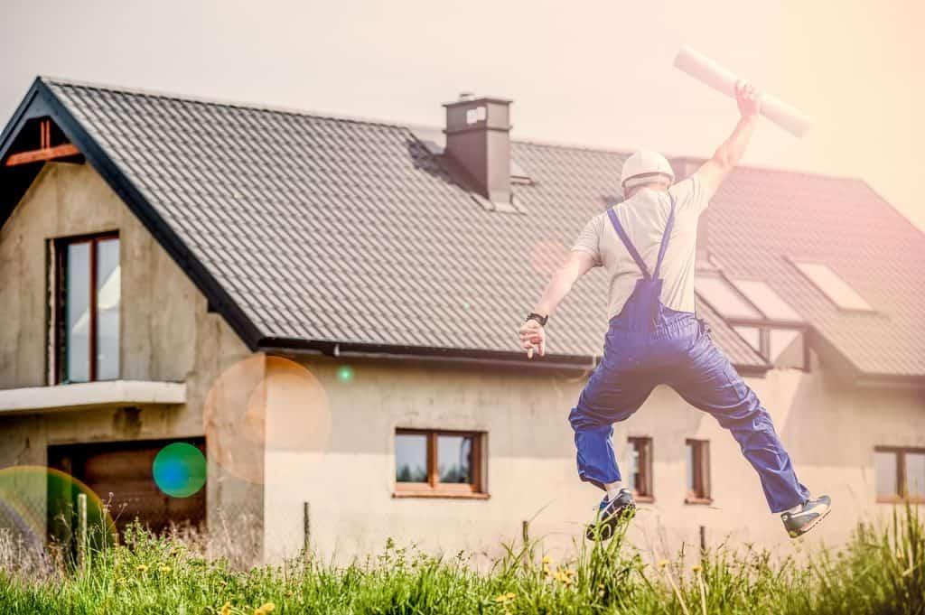 איש שיפוצים קופץ באוויר מול בית פרטי ומחזיק תוכנית עבודה