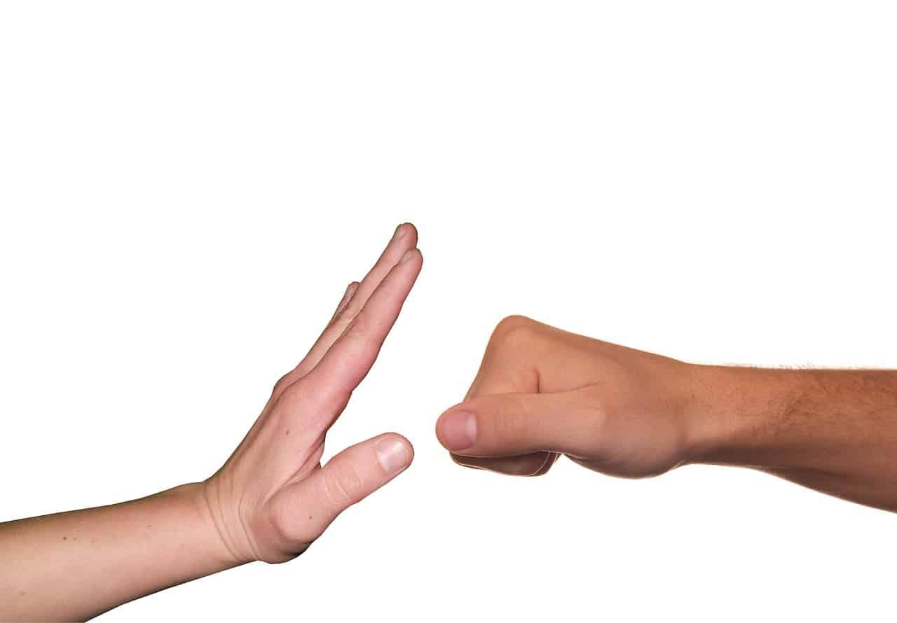 יד קפוצה לאגרוף ויד שניה מונעת את האגרוף
